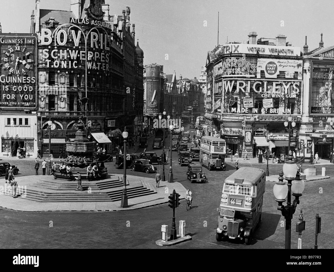 Iconic tourist attraction Piccadilly Circus as seen in the 1950s, a working traffic roundabout, surrounded by advertising - Stock Image