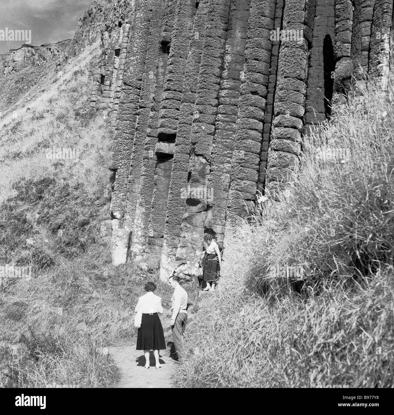 Visitors on a coastal path by a cok, a basalt rock formation at the ancient Giant's Causeway, County Antrim, - Stock Image