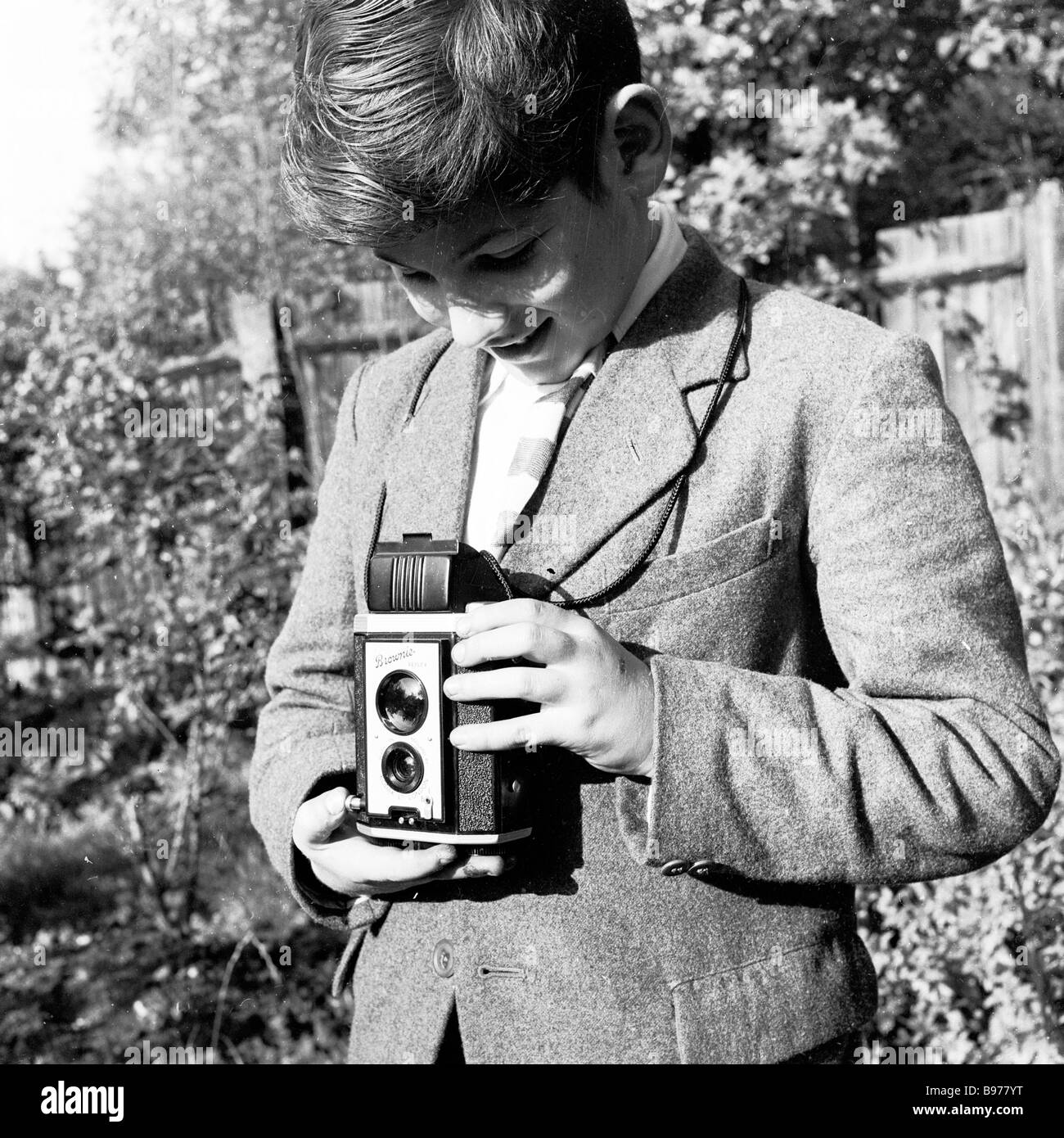 Looking down his viewfinder, a young boy in garden uses a Kodak Brownie reflex box film camera to take a photo, Stock Photo