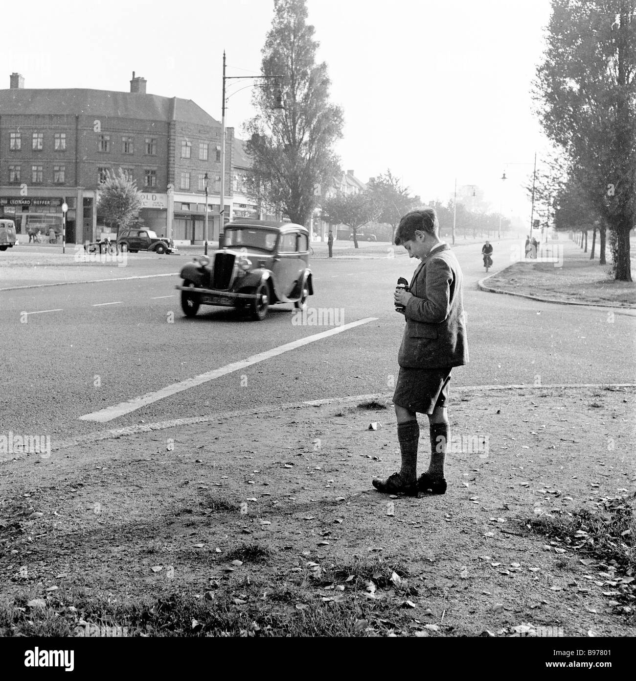 1950s, historical, young boy roadside taking pictures of moving cars with his Kodak Brownie Reflex' film camera. - Stock Image