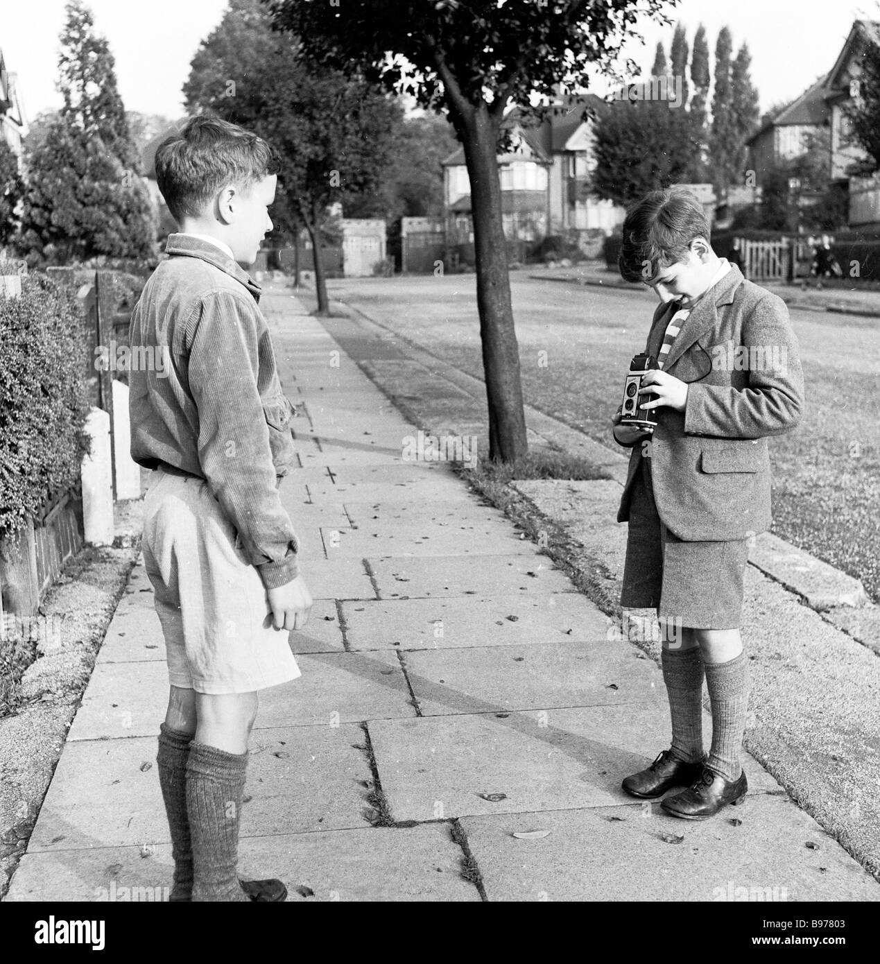 1950s, historical, young boy in school uniform taking a photograph of his school friend with a Kodak Brownie Reflex' - Stock Image