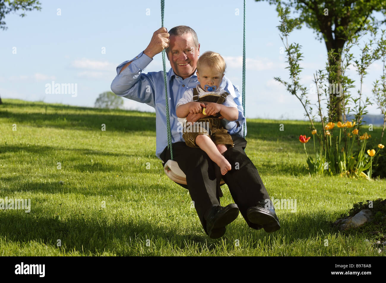 Grandfather with a child on a swing - Stock Image