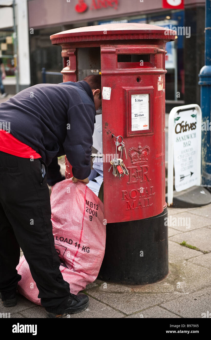 Female postal worker collecting letters from a red post office pillar box Aberystwyth Wales UK - Stock Image