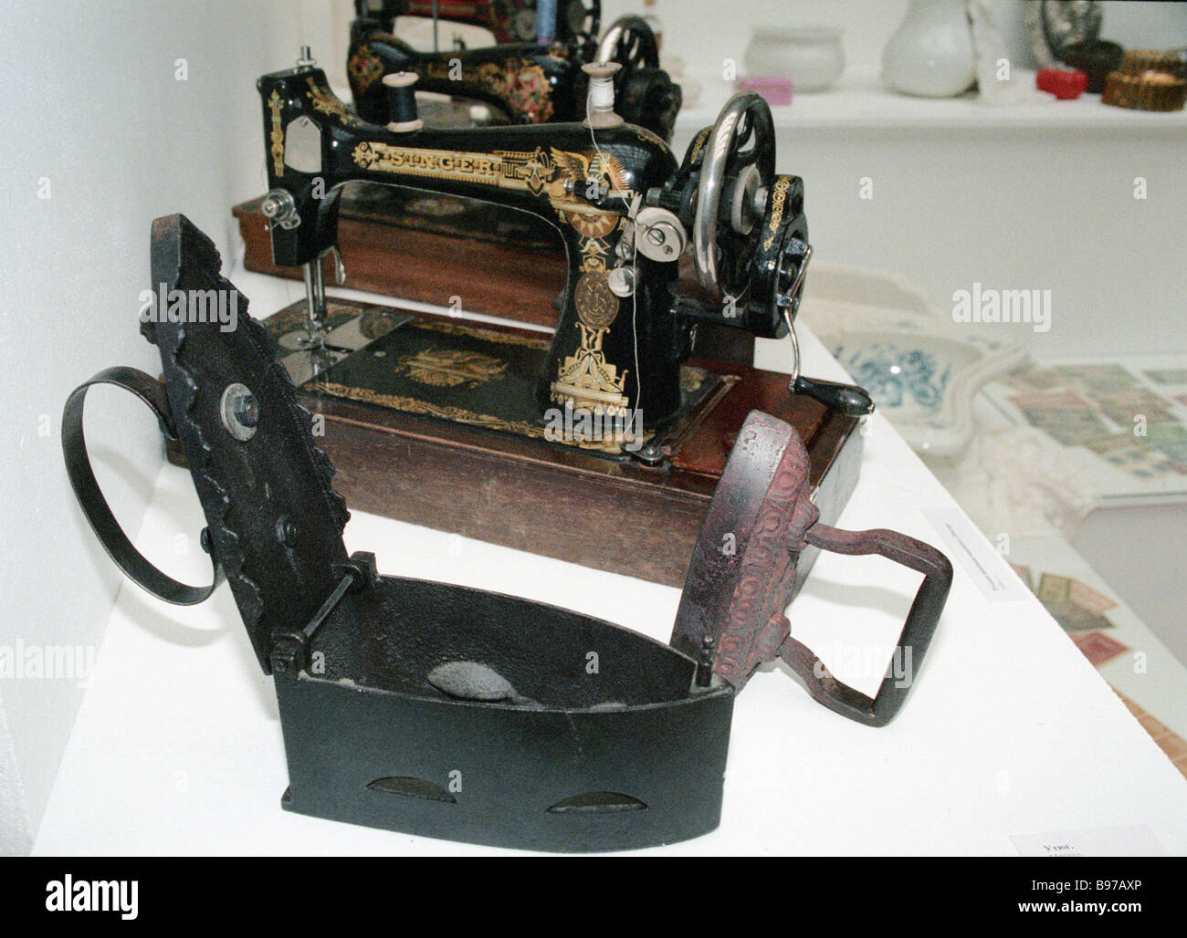 An early 20th century Zinger sewing machine and iron at the exhibition Good by to the 20th Century in the exhibition - Stock Image