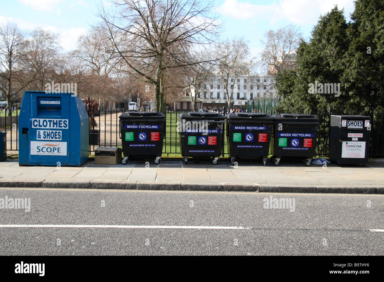 A road side recycling centre including bottle banks and containers for old clothes and shoes in Chelsea, London. - Stock Image