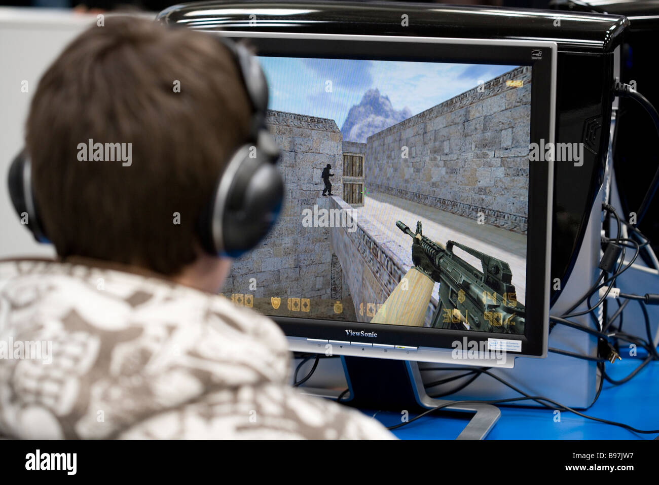 Teenager playing a violent game egoshooter at the computer - Stock Image