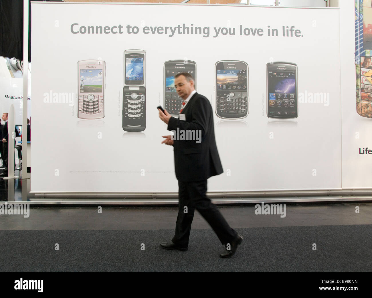 CeBIT businessman with smartphone in front of an advertising poster for various smartphones - Stock Image