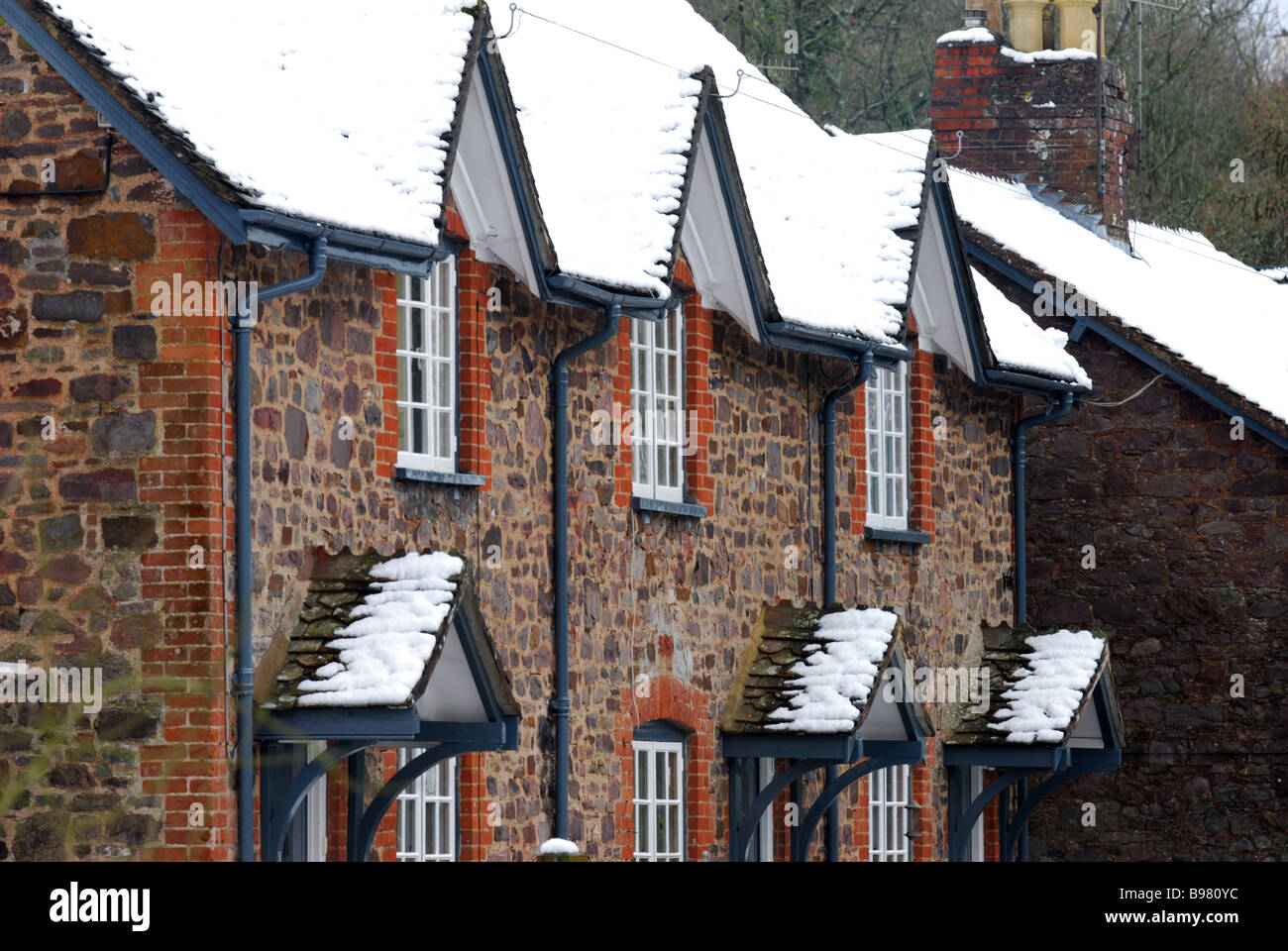 A dusting of snow on the rooftops of houses on the National Trusts Knightshayes court estate in Devon - Stock Image