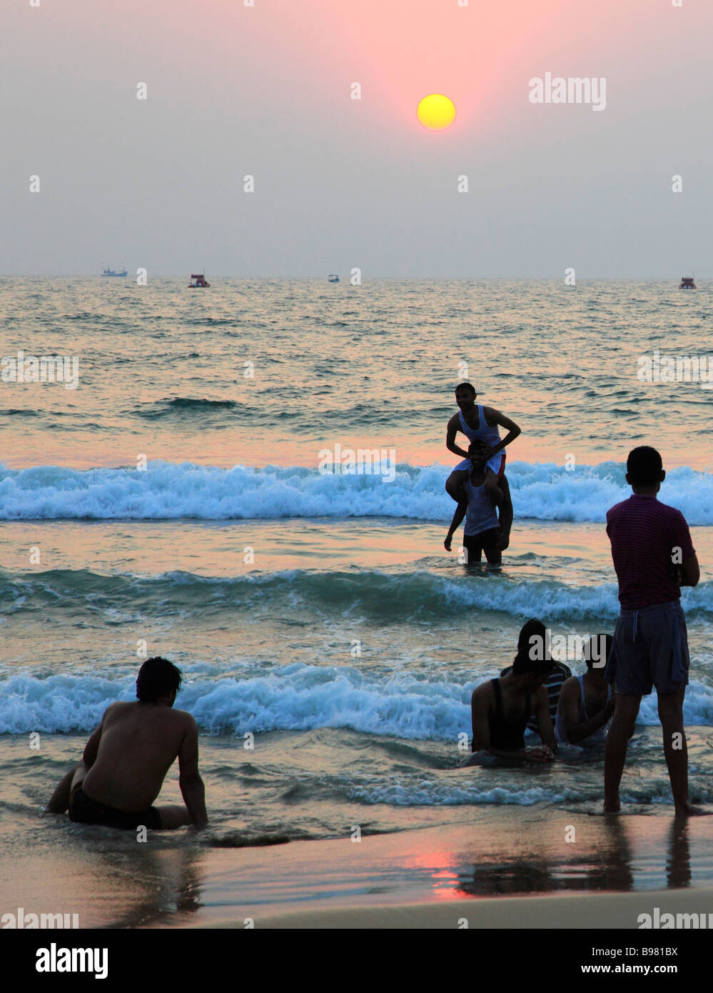 India Goa Colva beach sunset people bathing - Stock Image