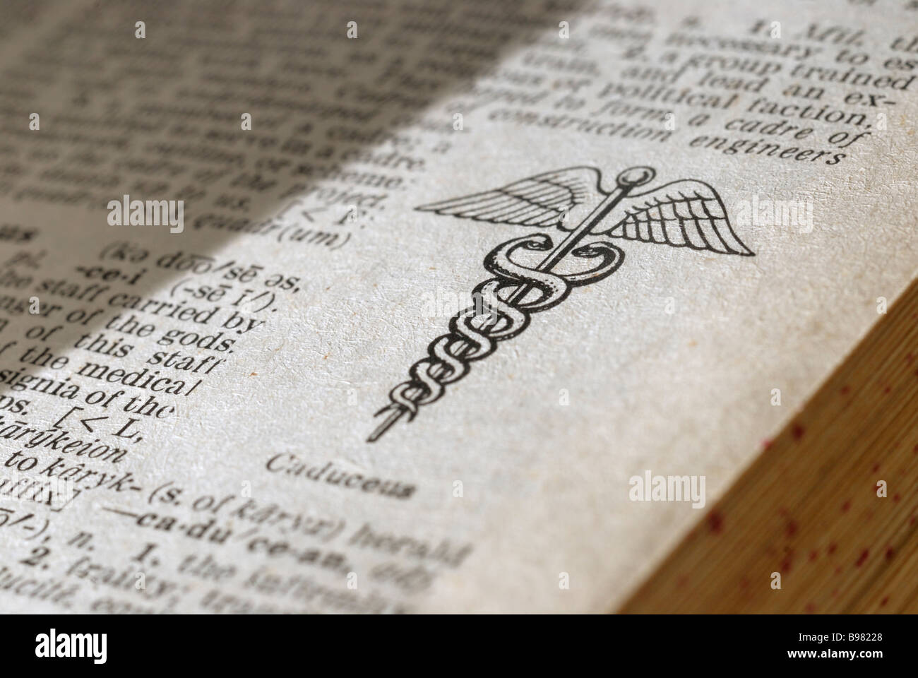 Caduceus symbol on a dictionary page - Stock Image