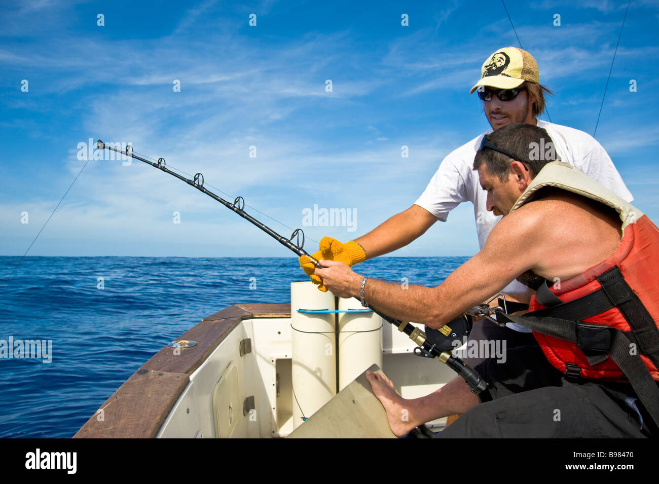 Big game fishing, fishermen on fishing boat Saint Gilles La Réunion France | Hochseeangeln, Fischer beim Drill, - Stock Image