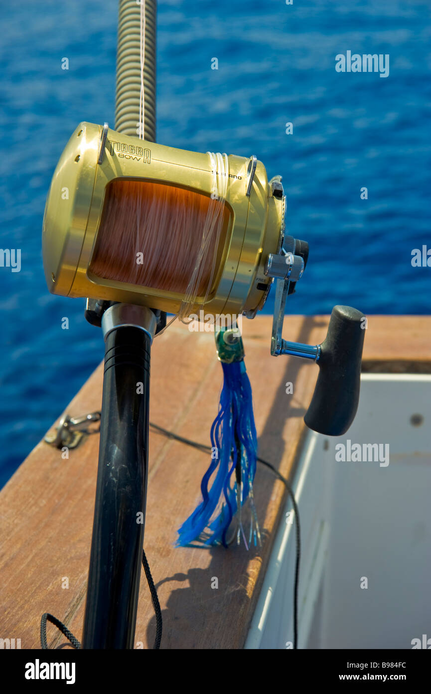 Fisching reel with lure on fishing boat La Réunion France | Rolle mit Köder und Angel auf Fischerboot, - Stock Image