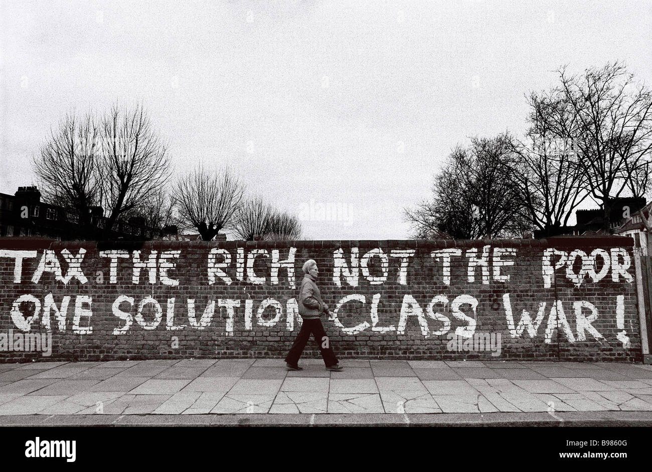 A woman walking past a slogan for Class War in Stamford Hill, North London in the late 1980's - Stock Image