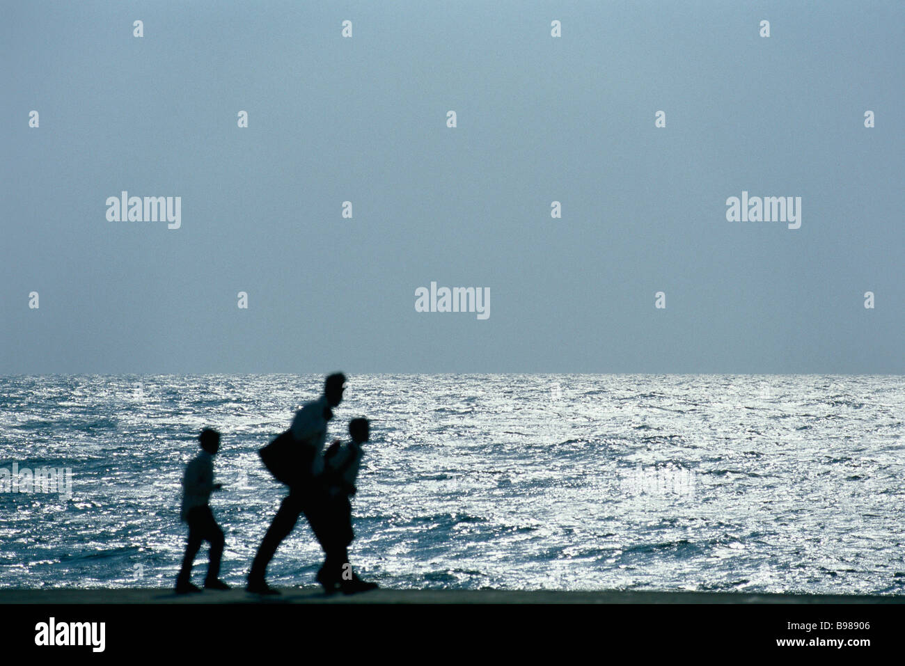 Man walking with two sons, silhouetted against ocean - Stock Image