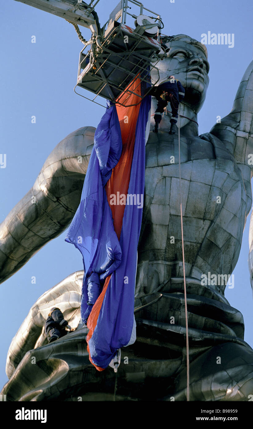 Decorating Vera Mukhina s Worker and Kolkhoz Woman monument with Russian tricolour ribbon - Stock Image
