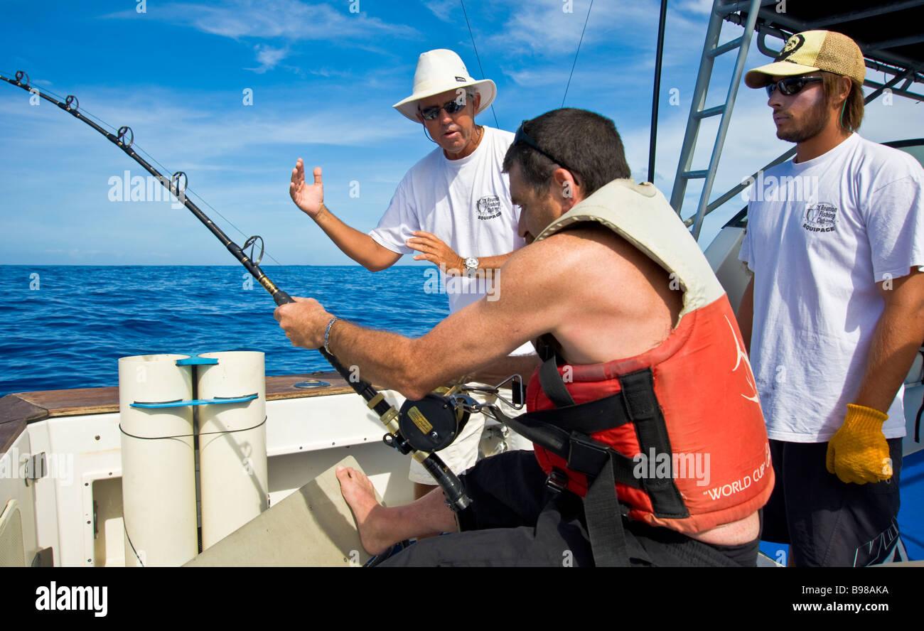Big game fishing, fishermen on fishing boat Saint Gilles La Réunion France | Hochseeangeln, Fischer beim Drill, Stock Photo