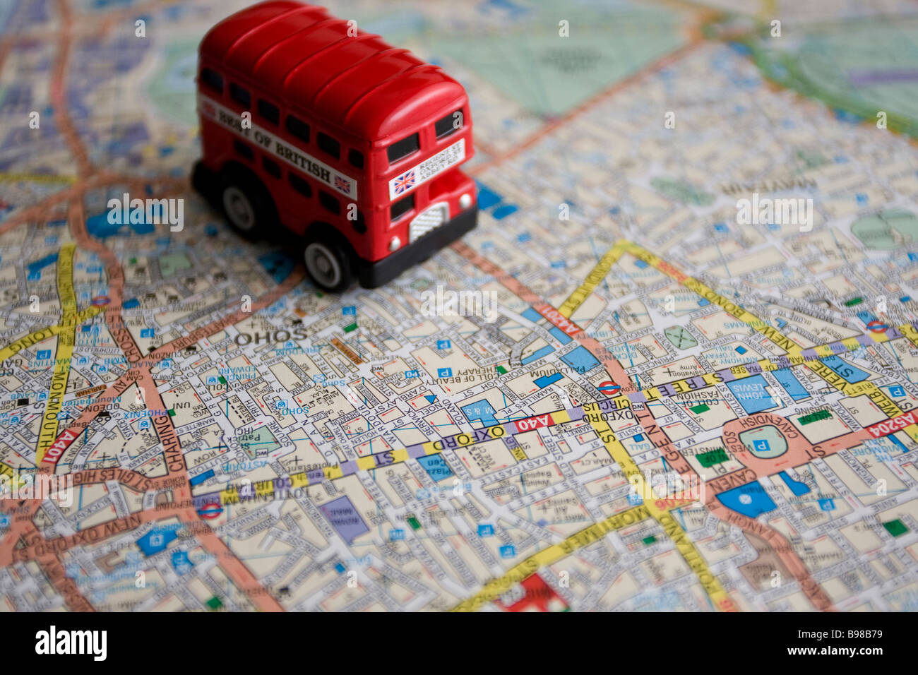 red double decker toy bus on london central map stock image