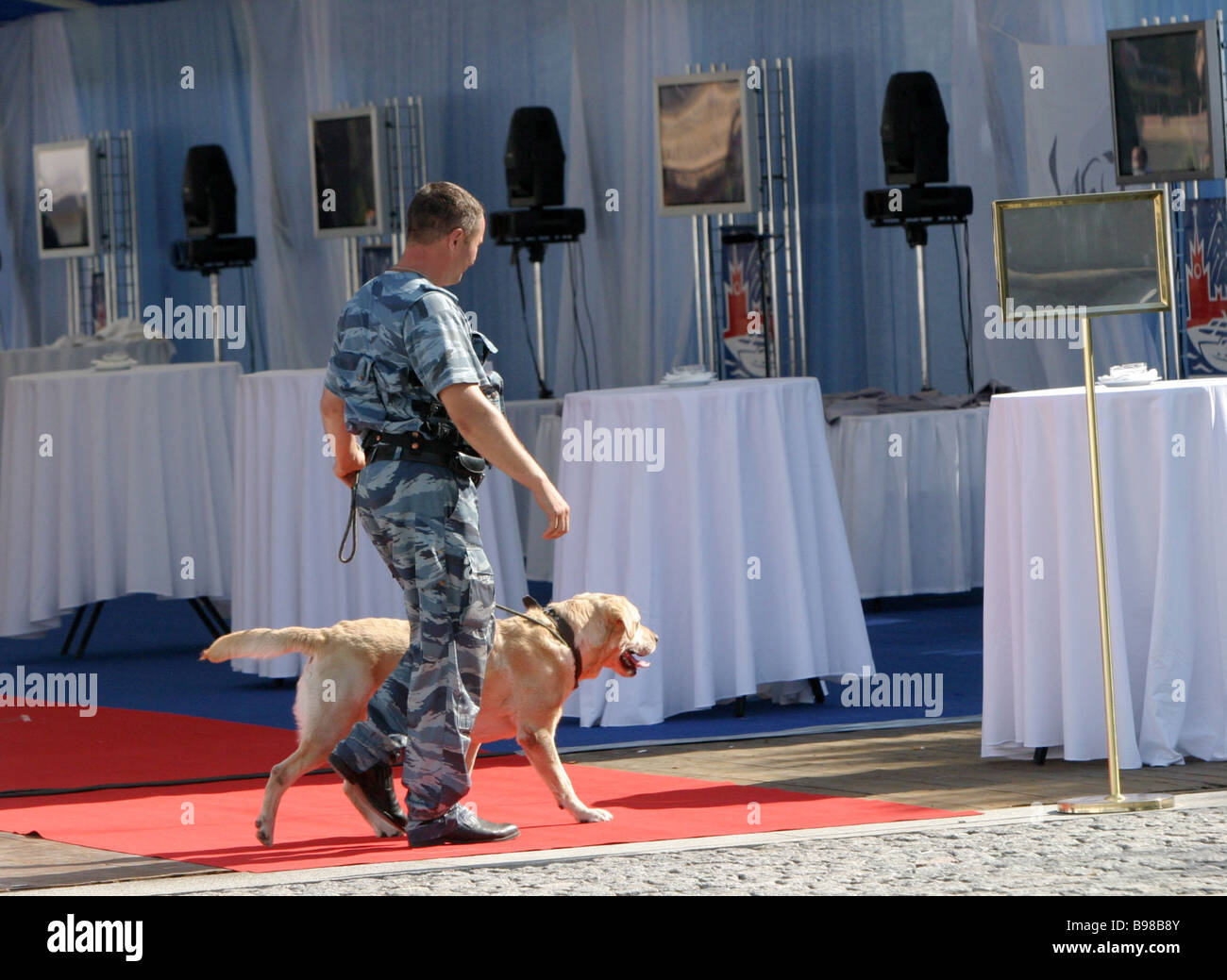 Trained dog and handler make a check before the opening gala of Moscow s maiden yachting festival - Stock Image