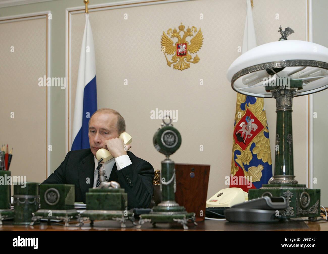 Russian President Vladimir Putin talks to Egyptian President Hosni Mubarak on the telephone at his Novo Ogaryovo - Stock Image