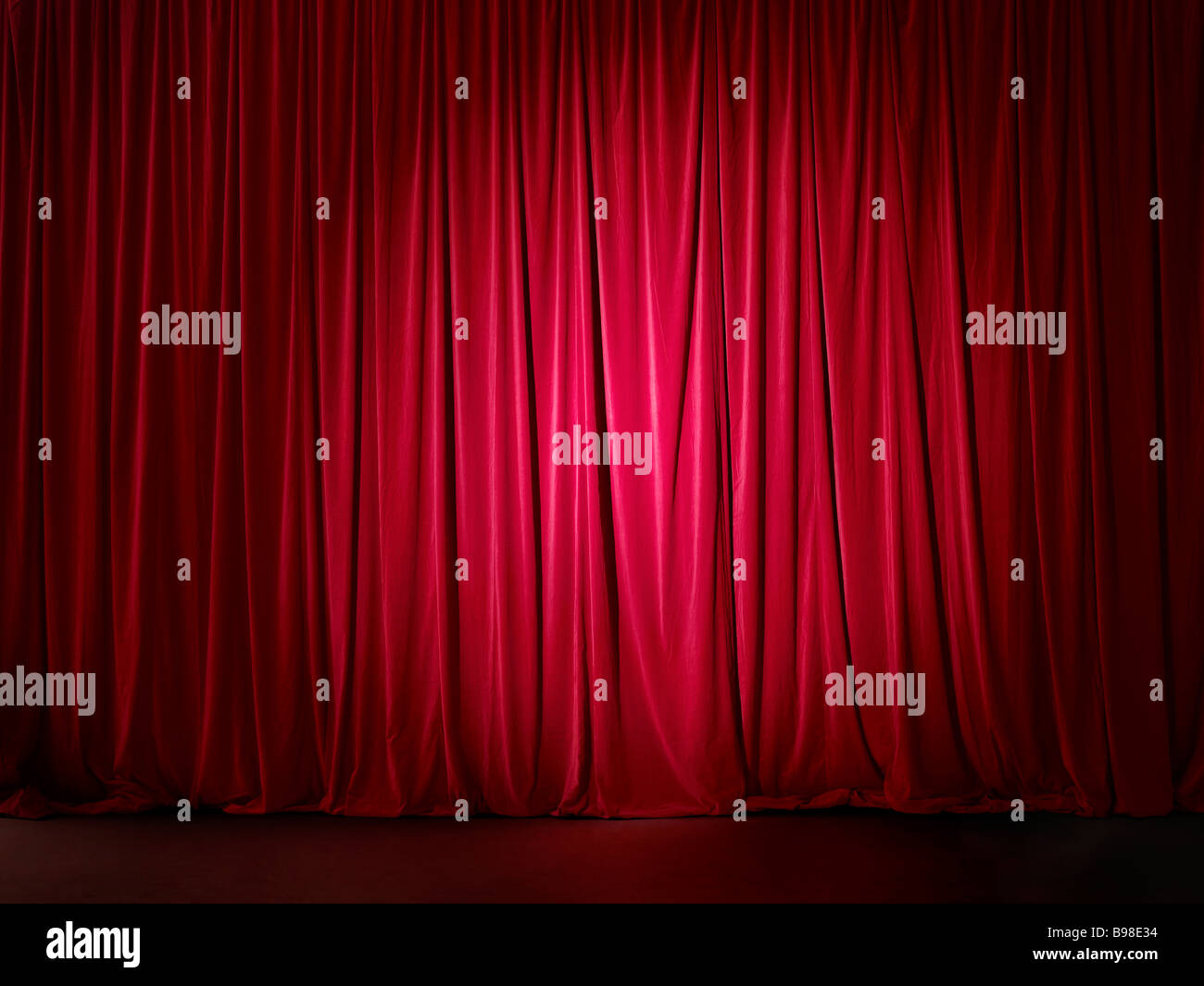 Red stage curtain spotlit - Stock Image