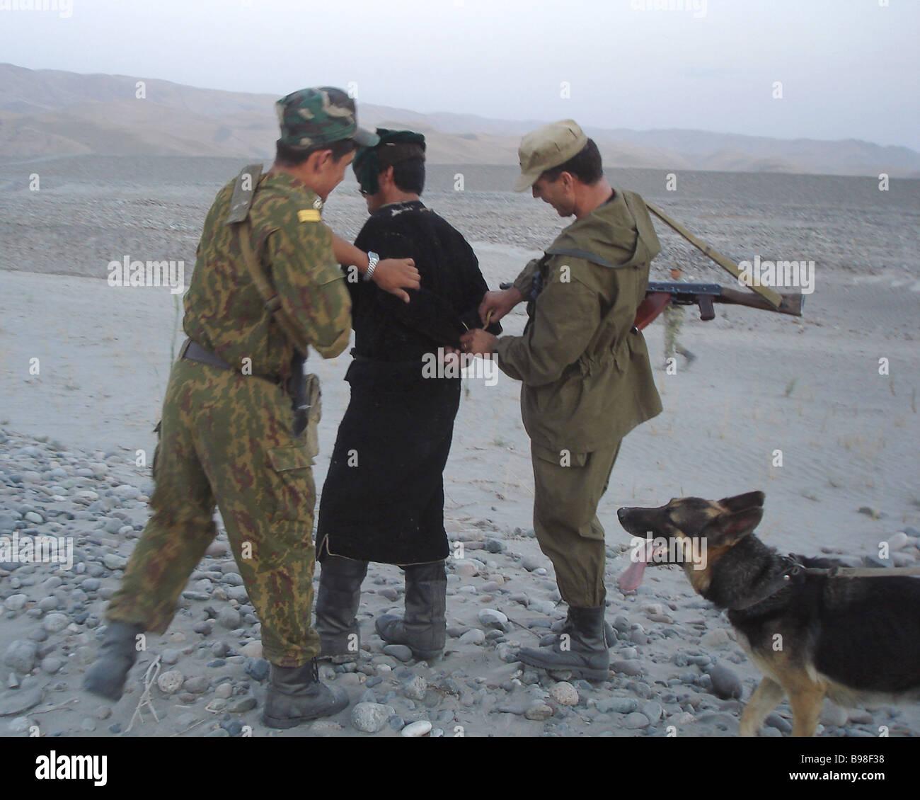 Detaining an Afghan drug smuggler on the Tajik Afghan border the area patrolling by the Pyandzhsky border guard - Stock Image