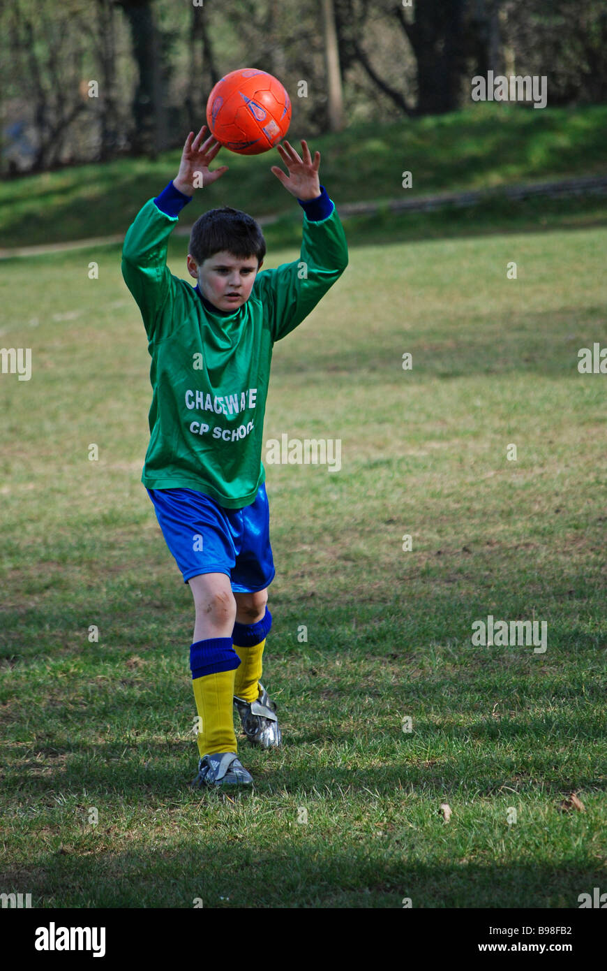 a young boy taking a 'throw in' during a footbal match - Stock Image