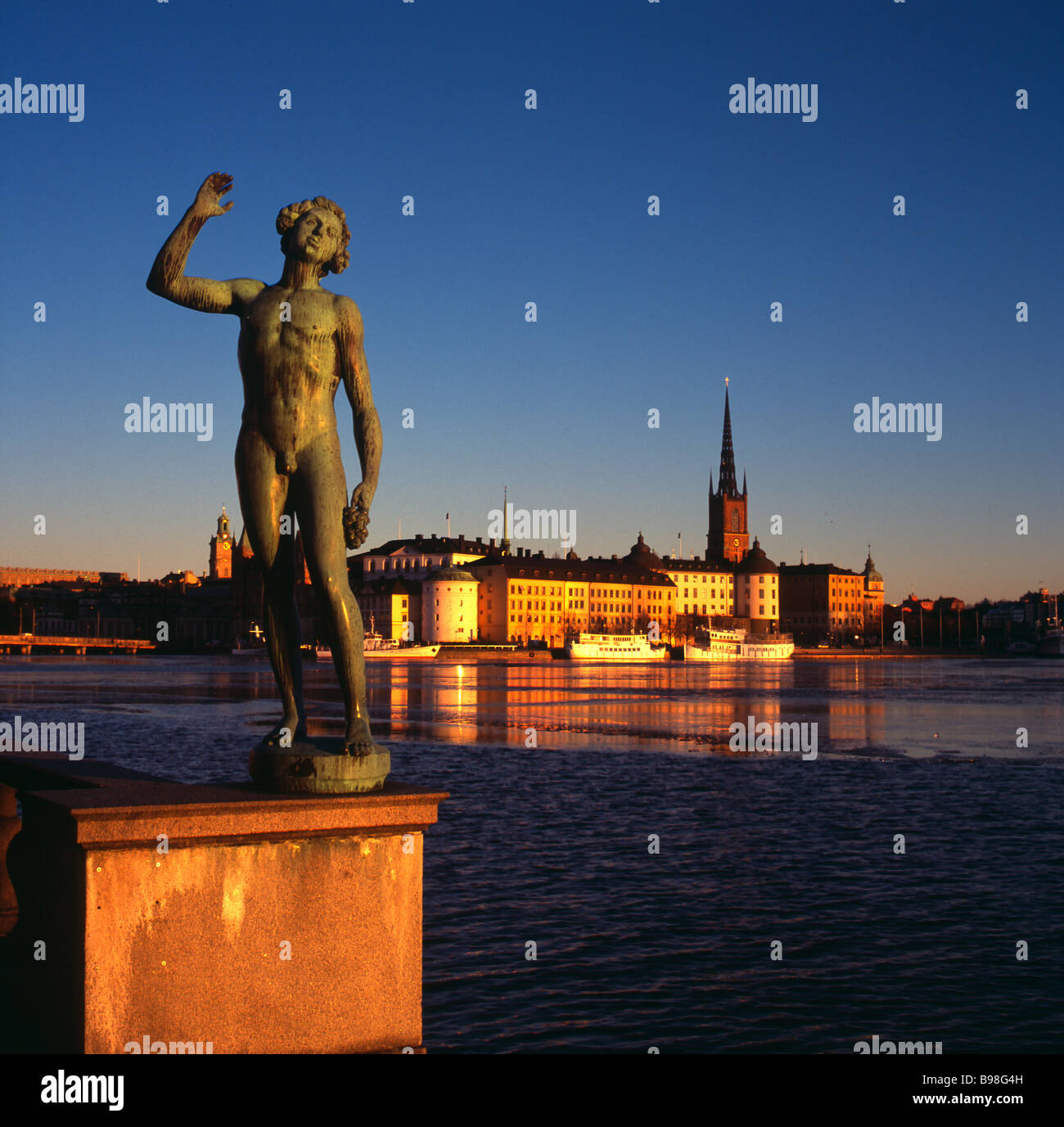 Statue on waterfront outside Stadhuset, Kingsholmen, Stockholm, with Riddarsholmen behind, Stockholm, Sweden. - Stock Image