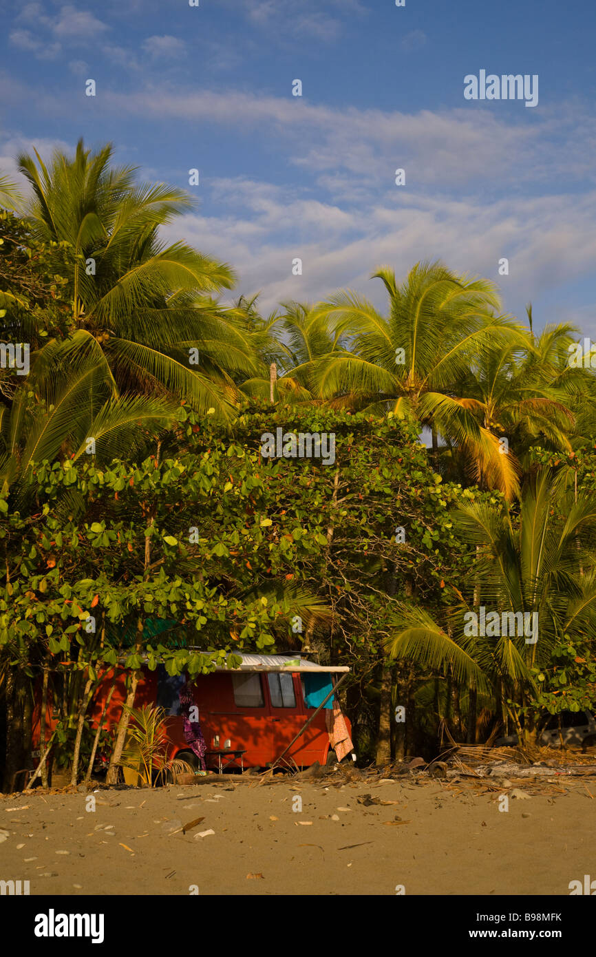 Orange Volkswagen van camping along the beach with palm trees in Dominical, Costa Rica. - Stock Image