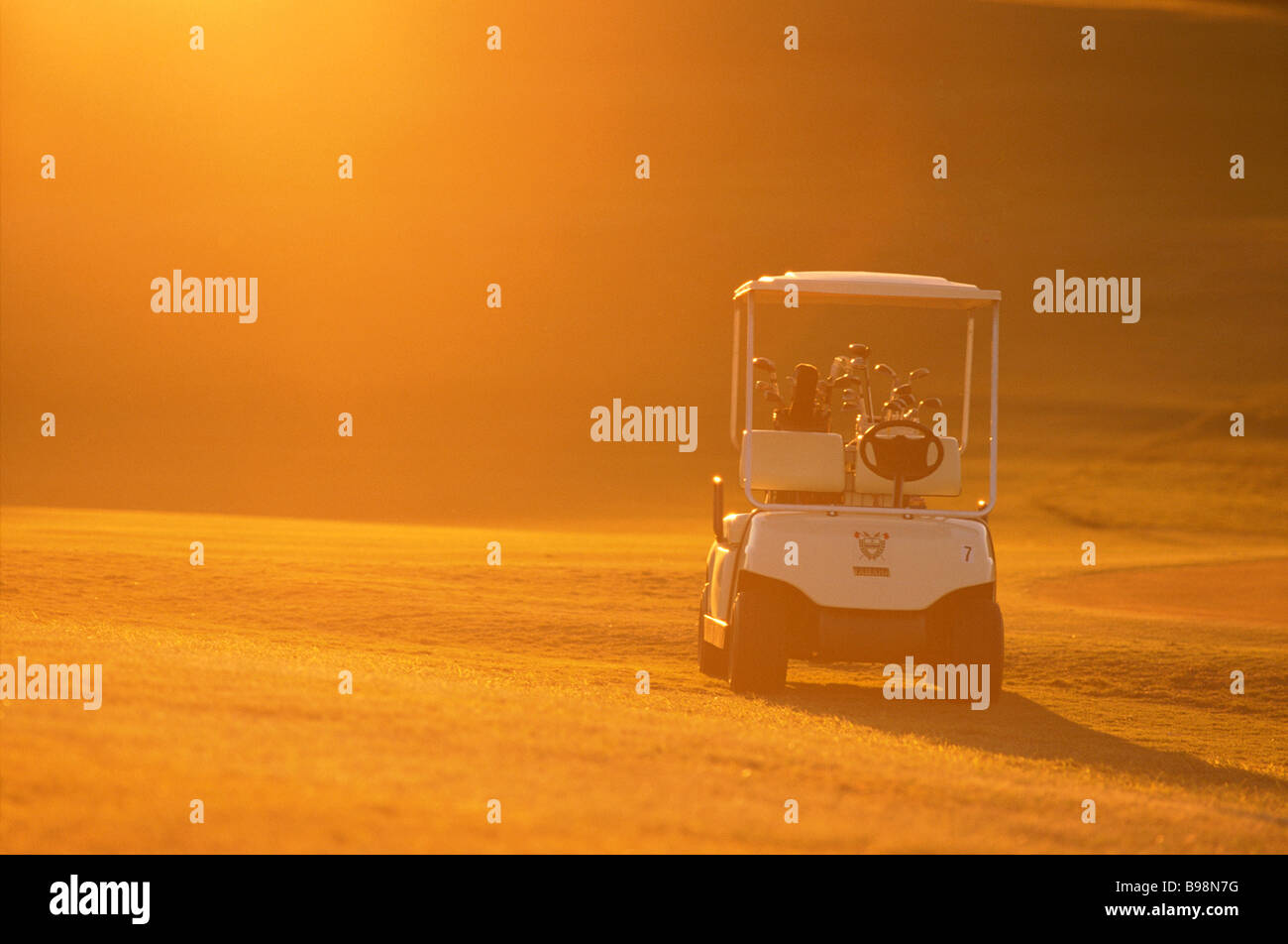 Golf buggy in sunrise - Stock Image