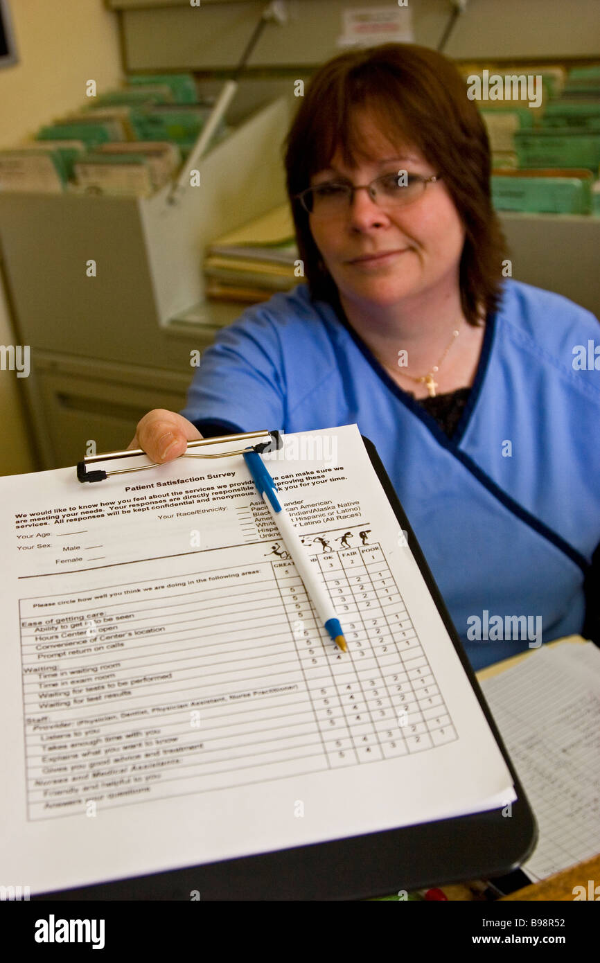 Woman, receptionist at doctor's office handing patient form on clipboard - Stock Image