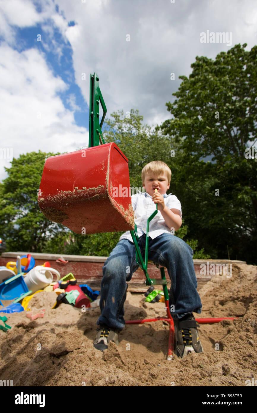 Boy playing in the sandbox. - Stock Image