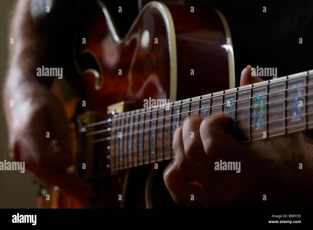 Guy playing electric jazz guitar - Stock Image