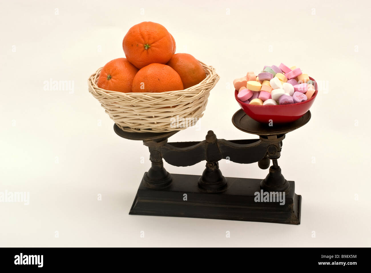 Balance scale with a basket of oranges on one side and a candy dish filled with candy on the other - Stock Image