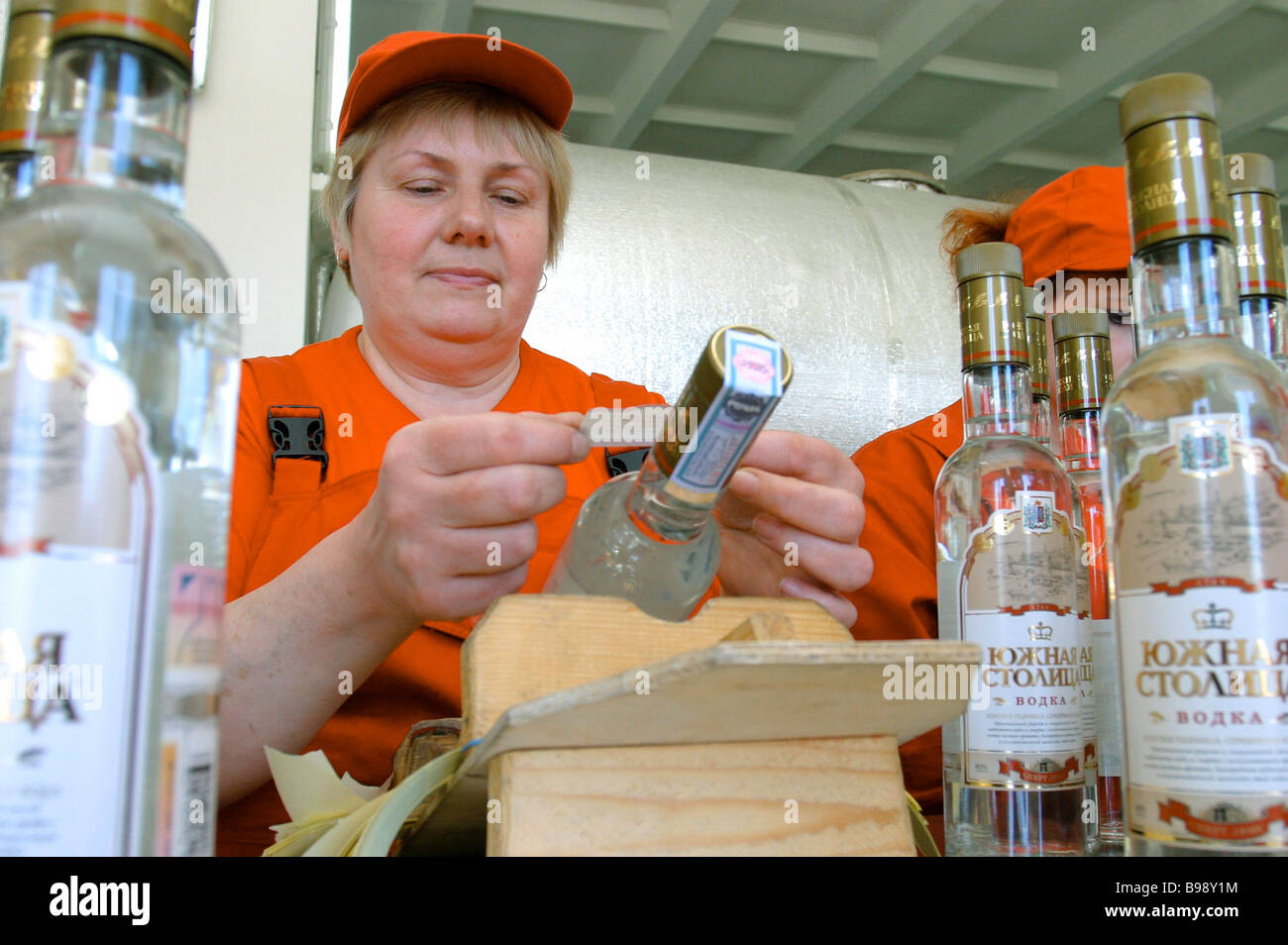 Pasting excise stamps and company labels on vodka bottles on a Yuzhnaya Stolitsa distillery conveyor line - Stock Image