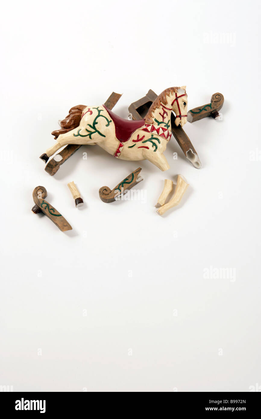 Broken rocking horse insurance toy - Stock Image