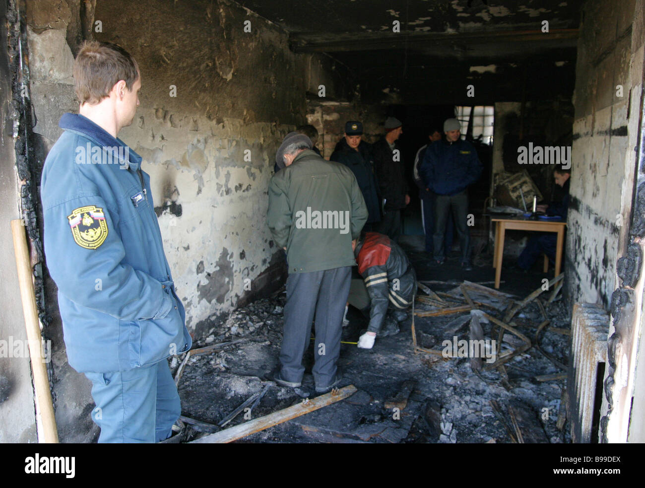 Police officers working at the site of a fire that gutted home for the elderly at Kamyshevatskaya stanitsa Cossack - Stock Image