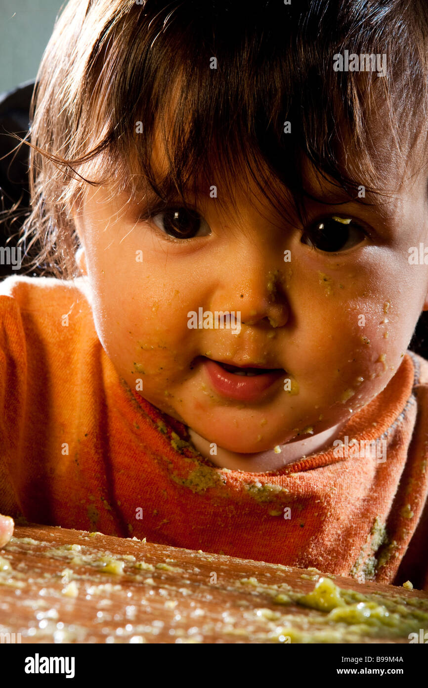 A nine month old baby eating and making a giant mess at the kitchen table - Stock Image