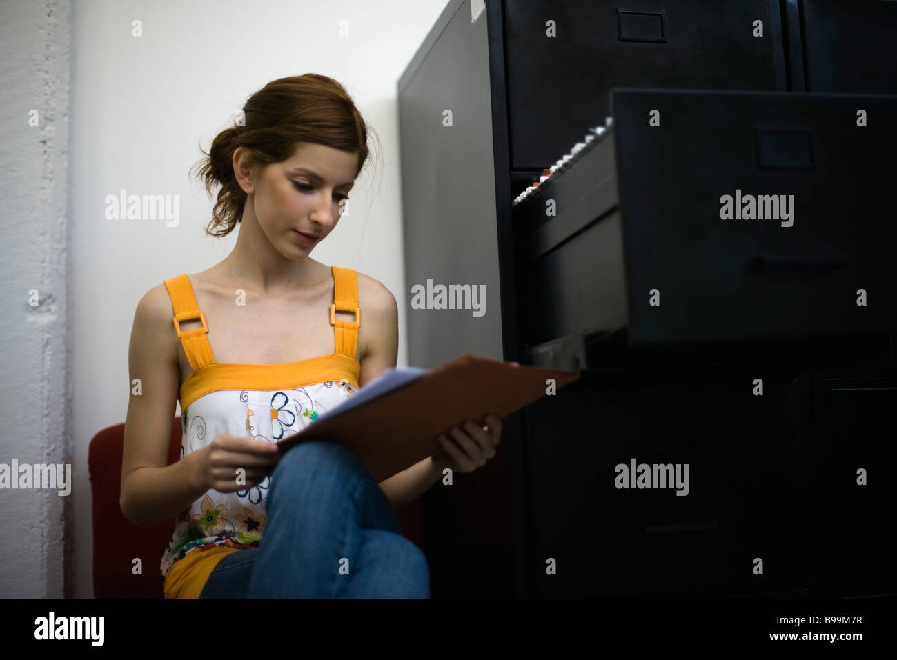 Woman reading document, sitting next to filing cabinet - Stock Image