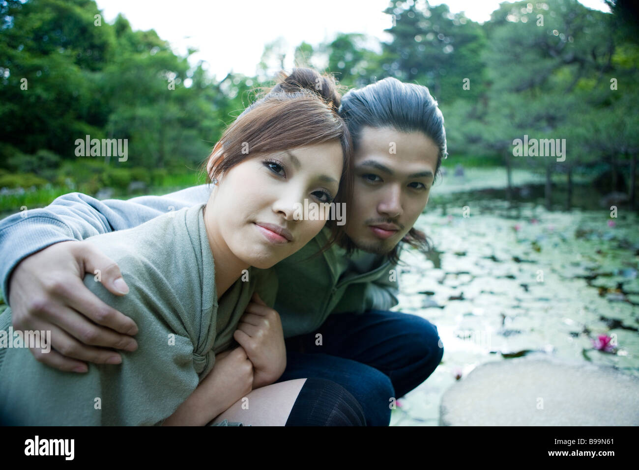 Young couple crouching beside pond, portrait - Stock Image