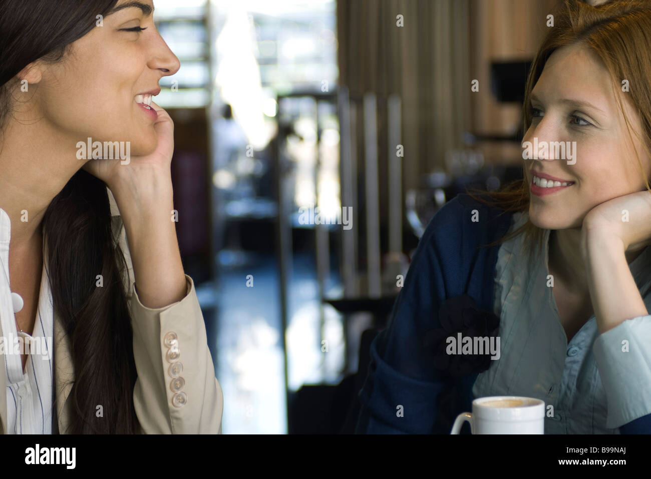 Two female friends having coffee and chatting in cafe - Stock Image