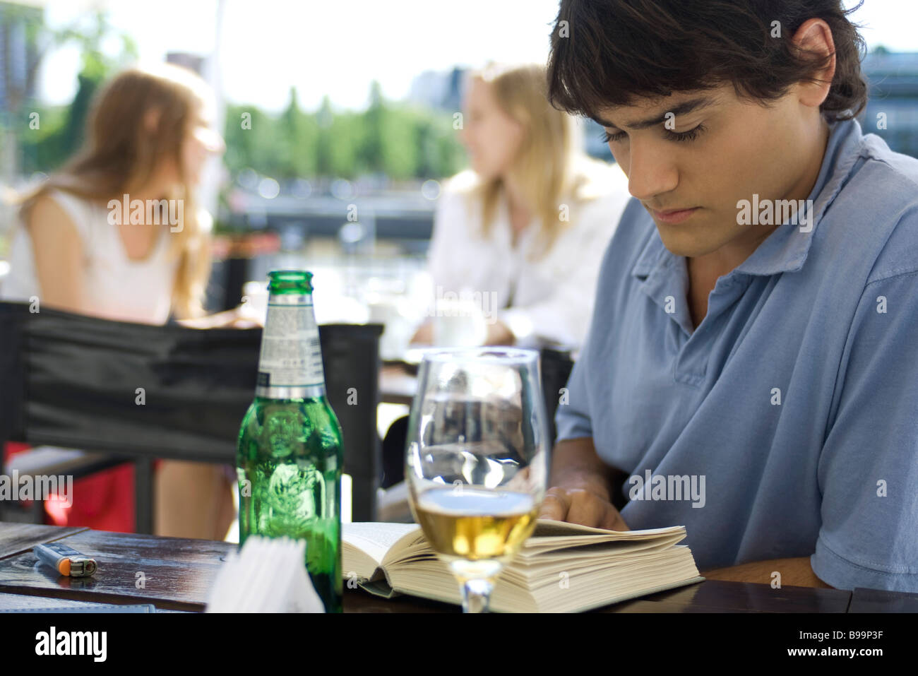 Young man sitting at outdoor cafe, reading book and having a beer - Stock Image