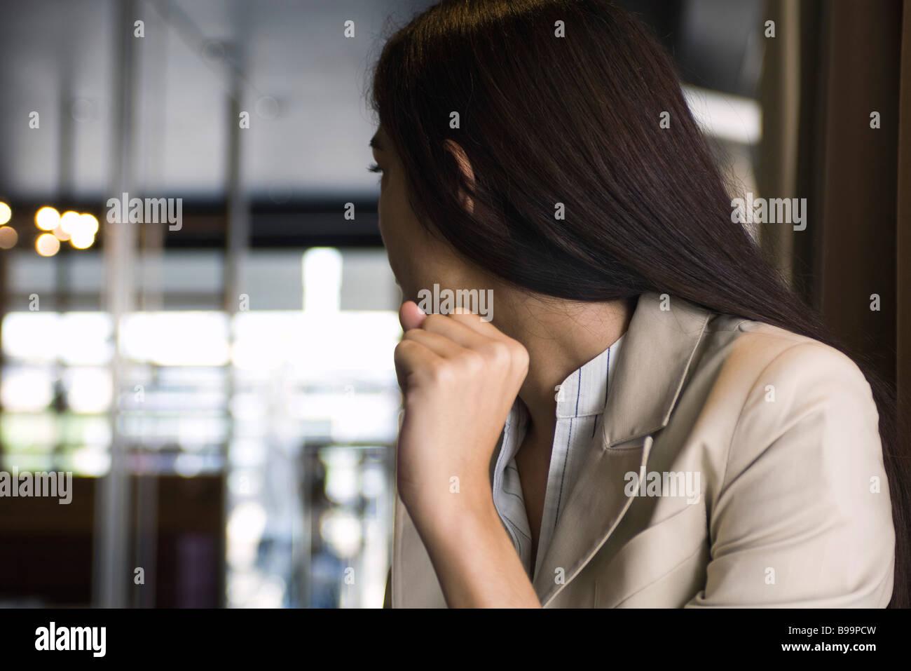Young woman in a restaurant, looking over shoulder toward door - Stock Image