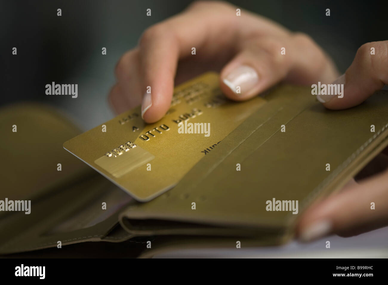 Woman's hand taking credit card out of wallet - Stock Image