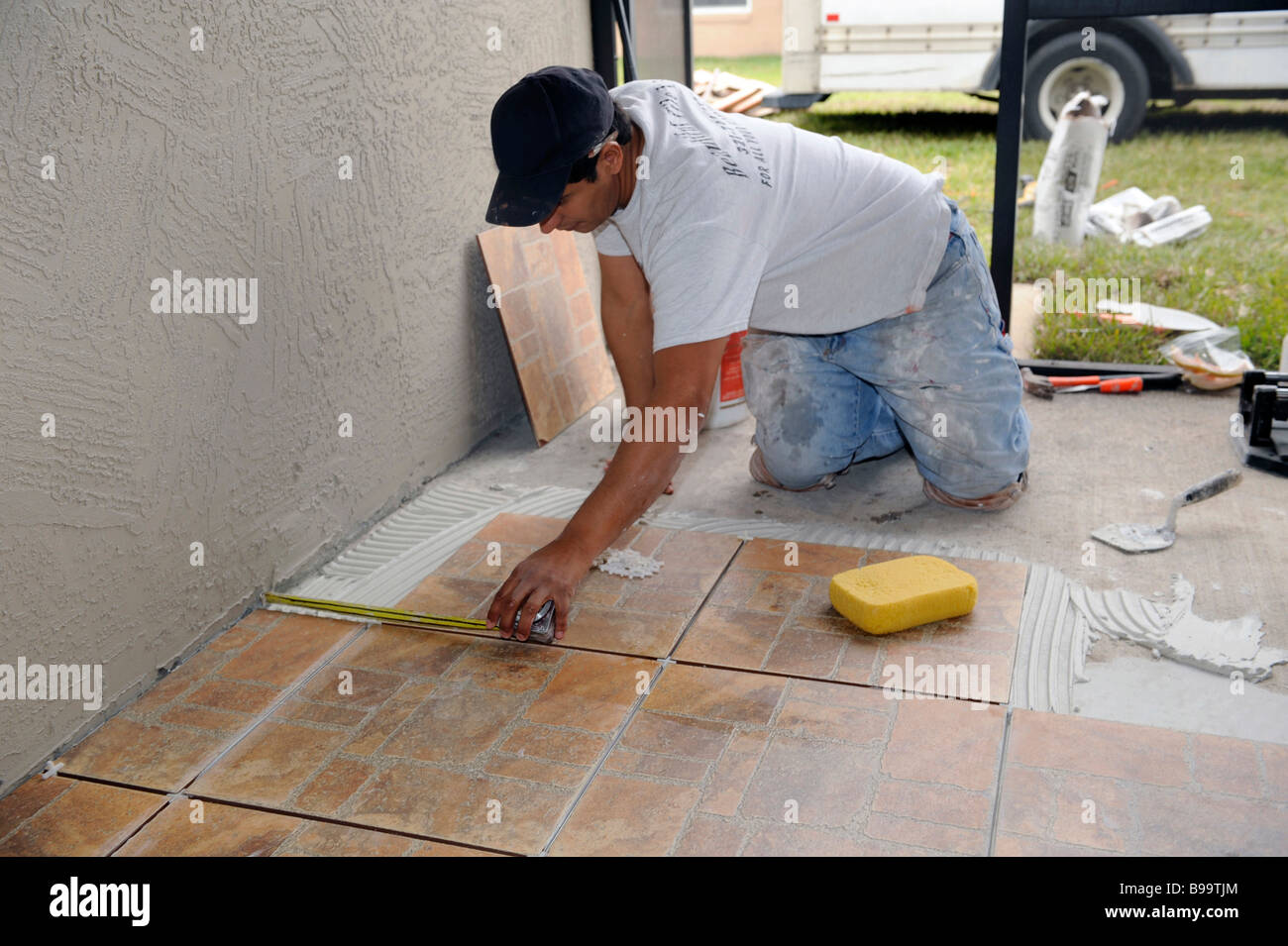 Male Hispanic Lays Ceramic Tile On Cement Floor In Patio Lanai