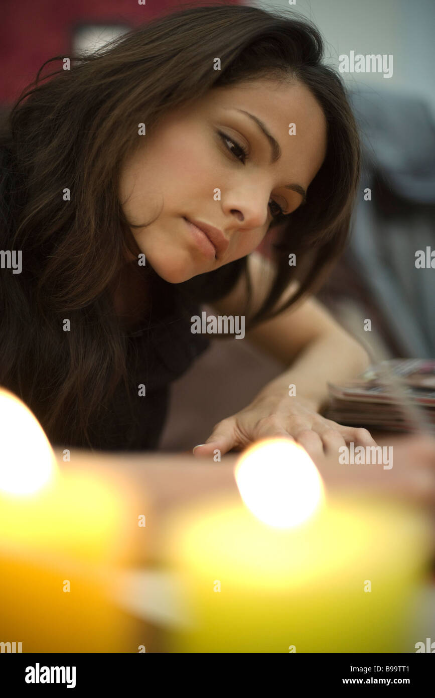 Woman writing, candles burning in foreground - Stock Image