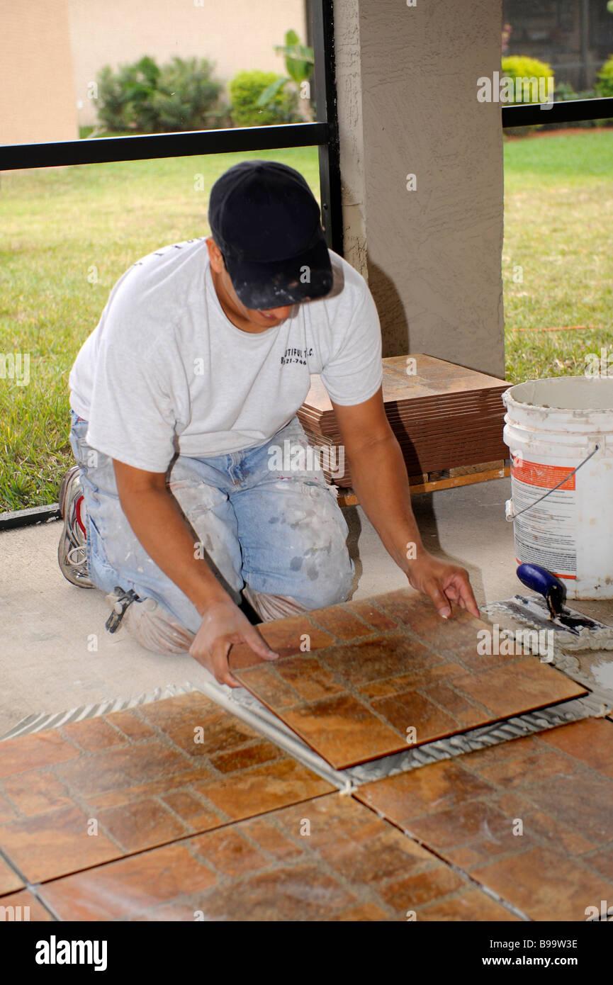 Male Hispanic Lays Ceramic Tile On Cement Floor In Patio Lanai