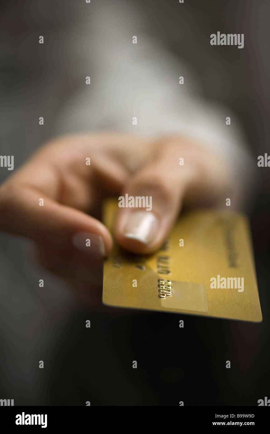 Woman's hand holding out credit card, extreme close-up - Stock Image