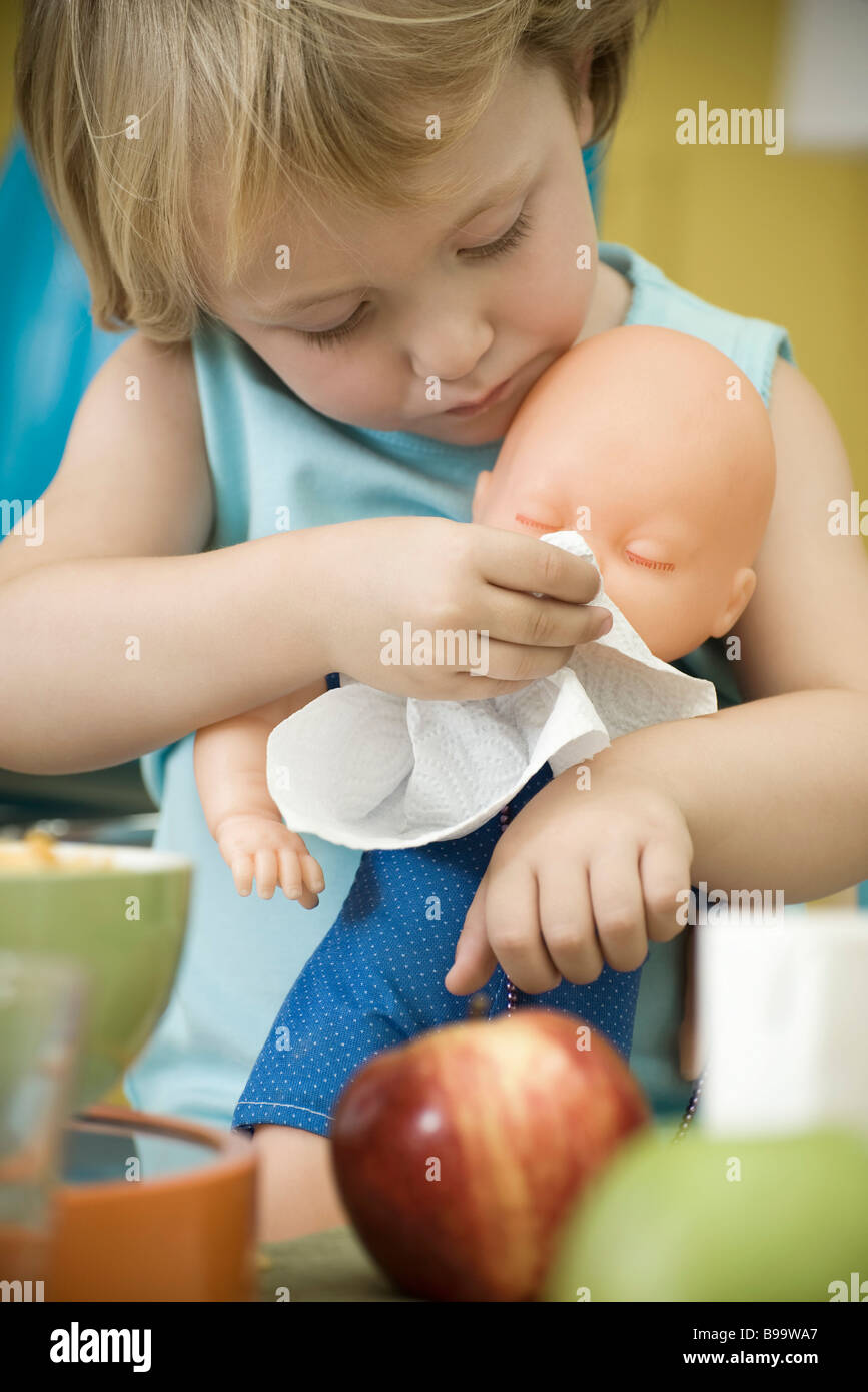Little girl wiping baby doll's face with paper towel - Stock Image
