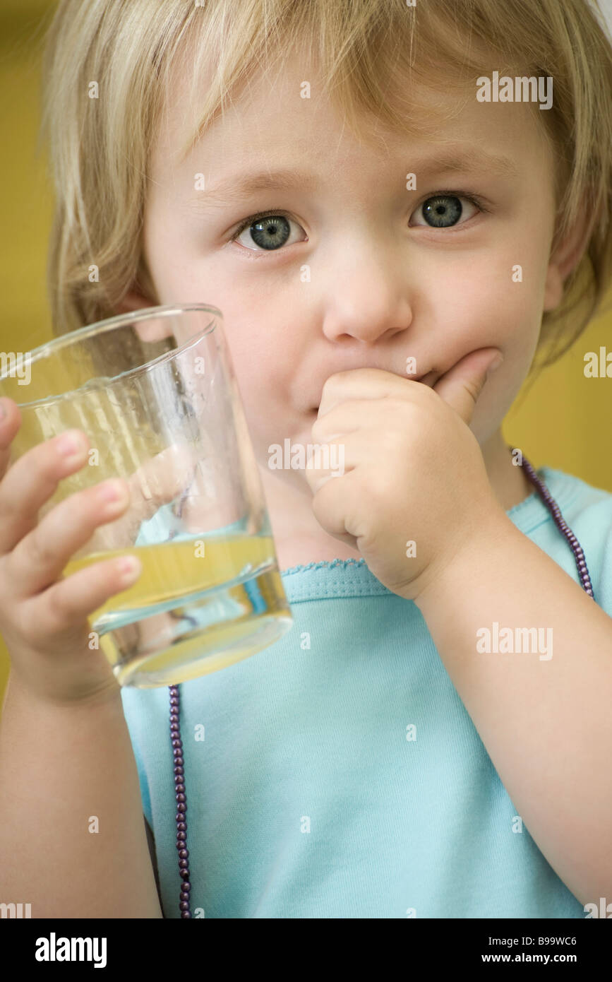 Toddler girl holding glass of juice, covering mouth with one hand Stock Photo