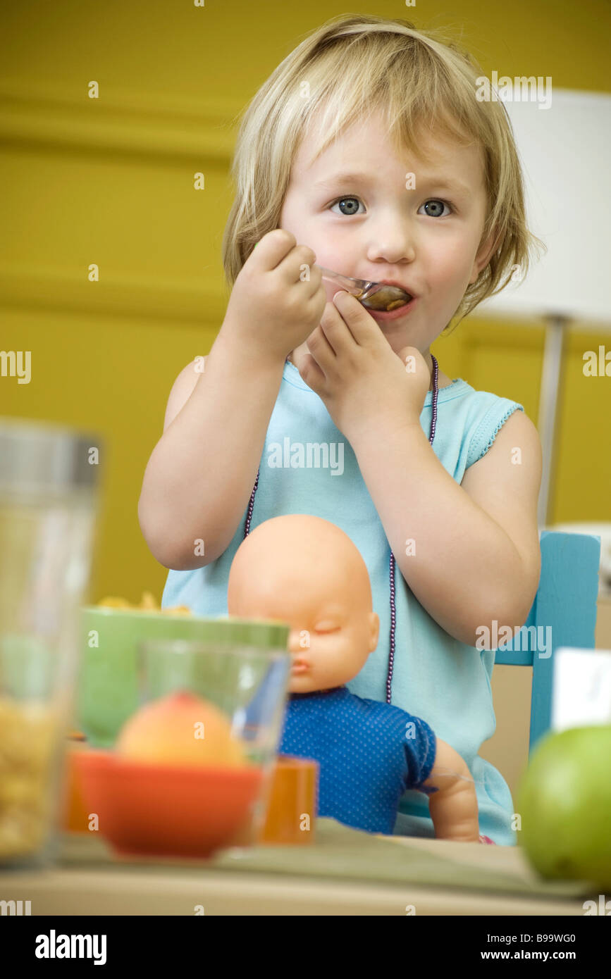 Toddler girl eating at table, baby doll in lap - Stock Image